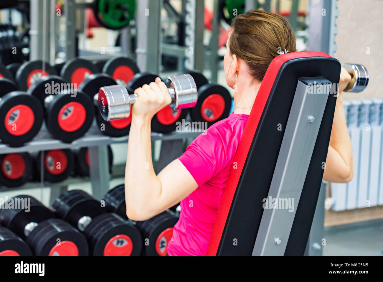 Back view young woman trains deltoid in gym Stock Photo