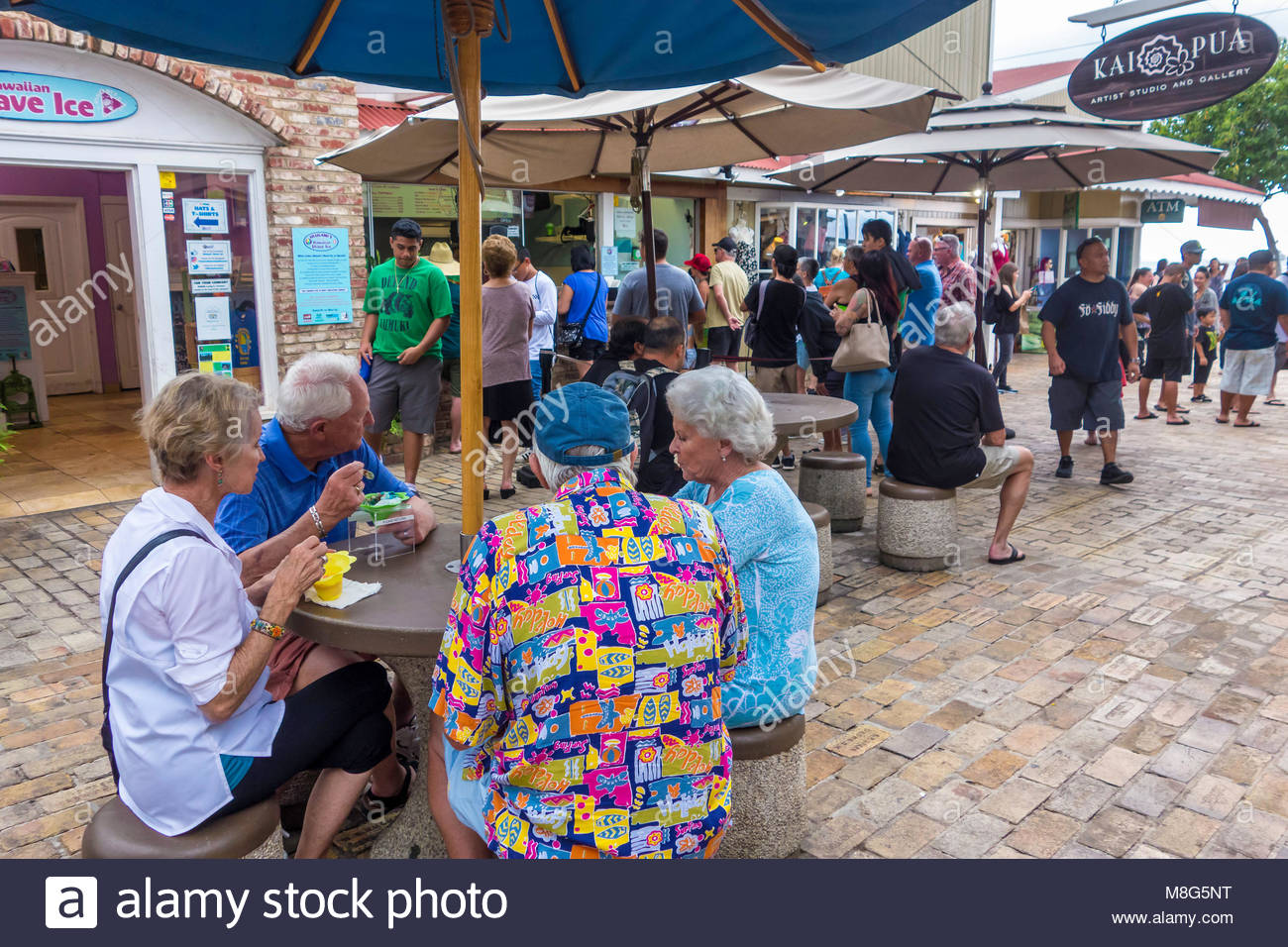 Tourists with Hawaiian shirt eating in food court off Front Street at Lahaina on the island of Maui in the state - Stock Image
