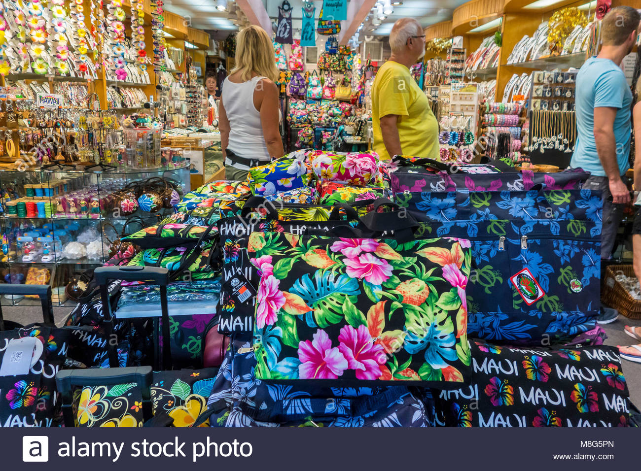 Kitsch Hawaiian souvenirs on Front Street with tourists shopping at Lahaina on the island of Maui in the state of - Stock Image