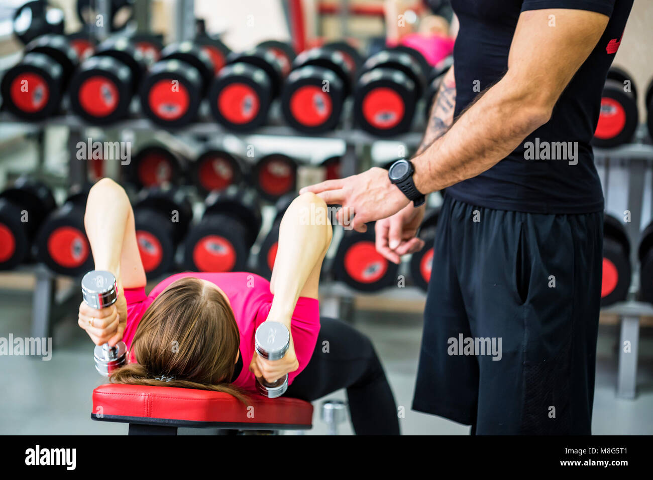 Young woman trains triceps with trainer in gym Stock Photo