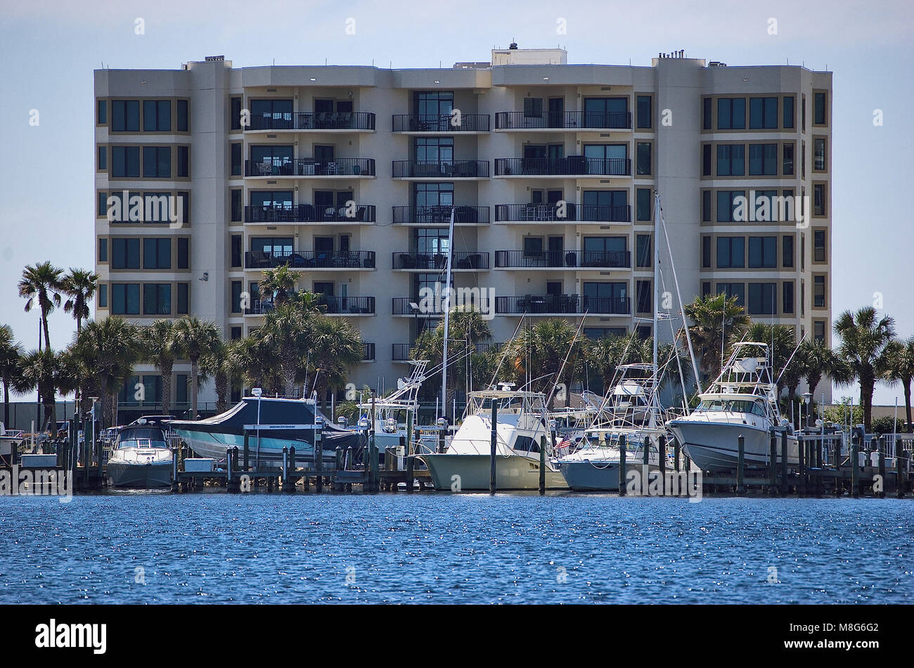A condo unit on the coast with private boats parked in front - Stock Image