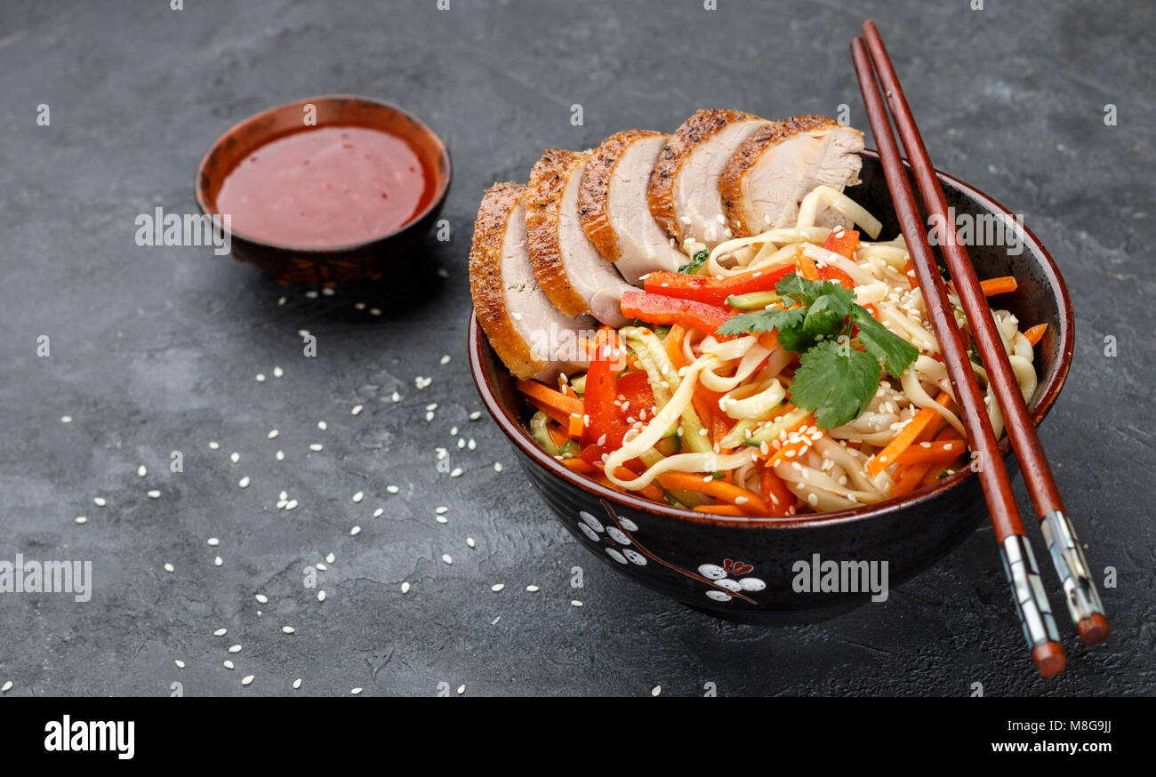 Udon noodles with vegetables (carrots, peppers, zucchini, cucumber, onion, cilantro, garlic), duck and sesame seeds. Stock Photo