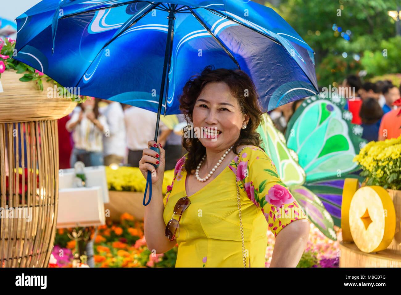 A Vietnamese woman wearing a yellow dress and holding a blue parasol, Ho Chi Minh City, Saigon, Vietnam Stock Photo