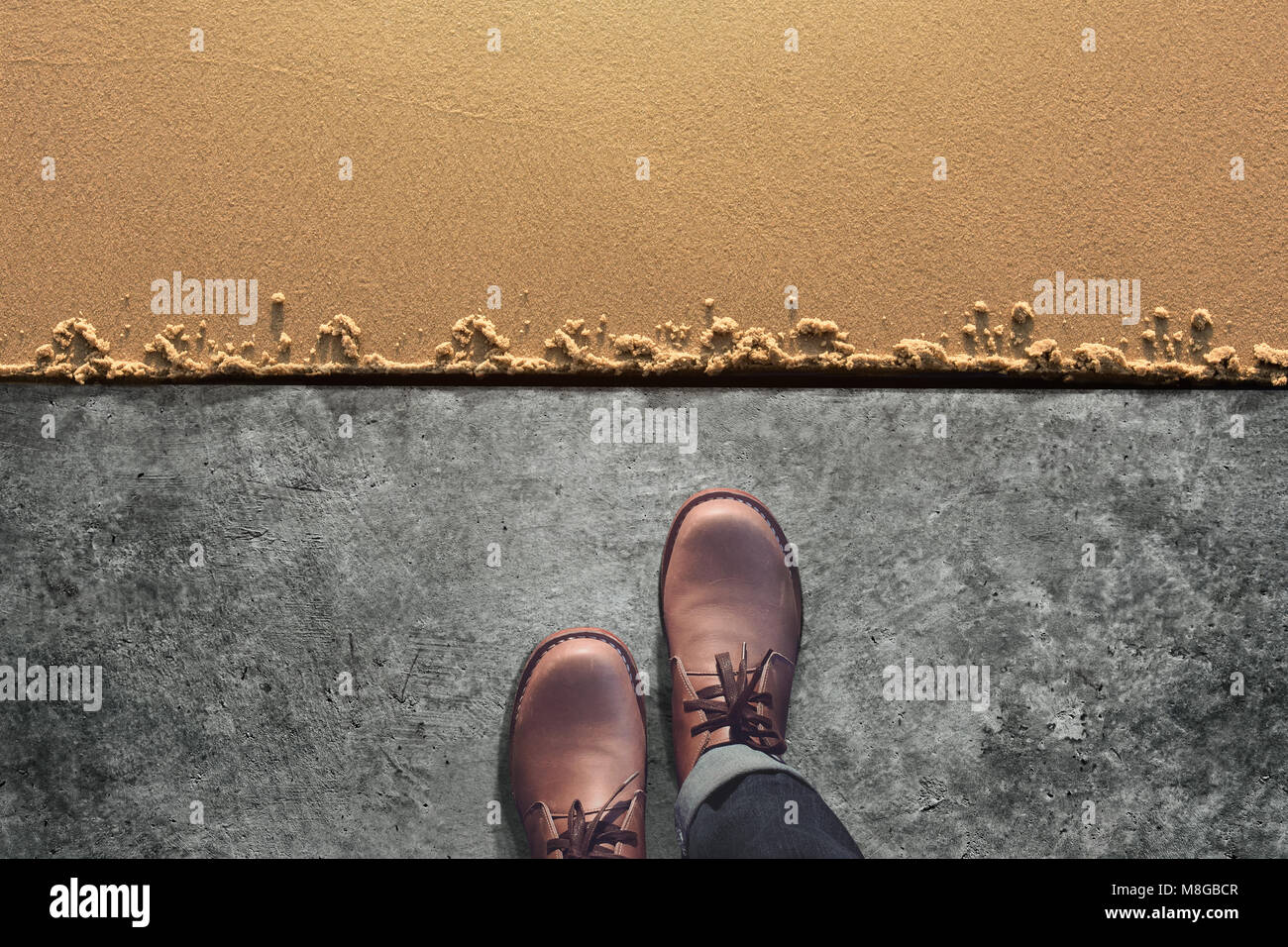 Comfort Zone Concept, Male with Leather Shoes Steps from Cement Floor into Sand Beach. Top View Stock Photo