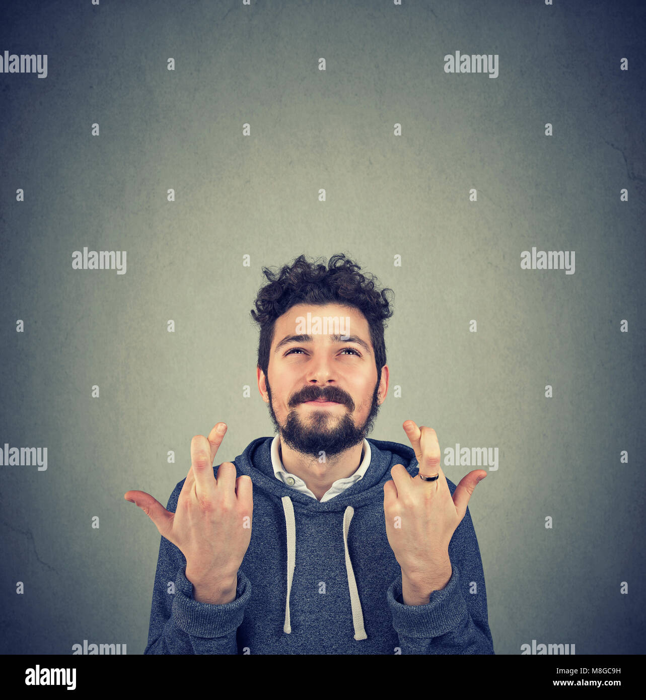 Young man crossing fingers and making a wish with great feeling of hope. - Stock Image