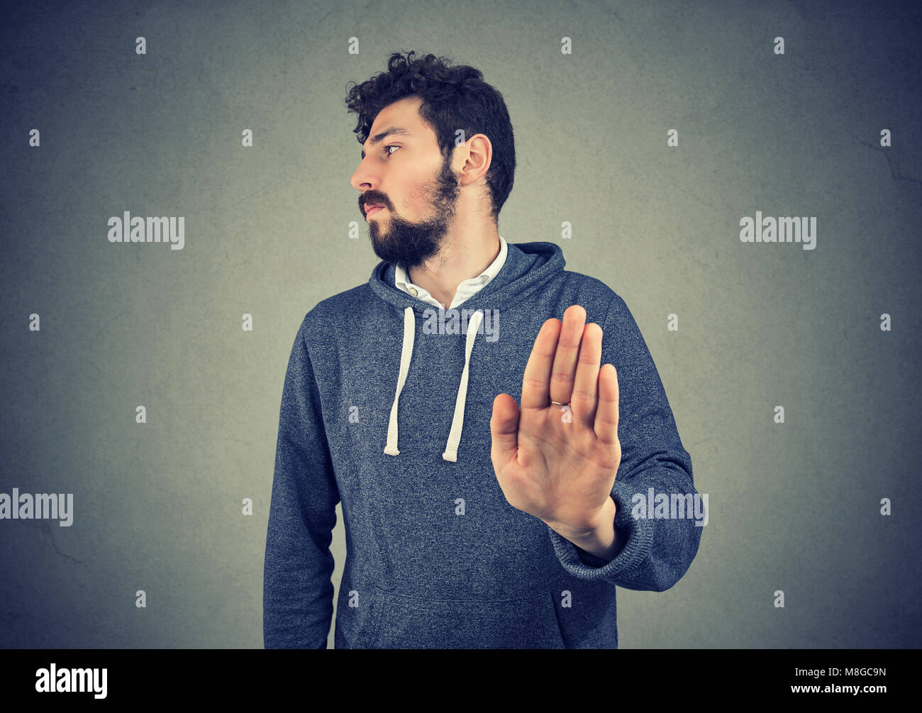 Annoyed angry man with bad attitude giving talk to hand gesture isolated on gray background. Negative emotion face - Stock Image