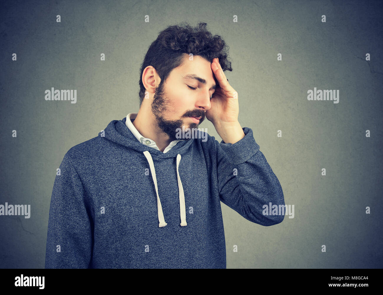 Young casual hipster with beard suffering from misfortune looking tired while rubbing head. - Stock Image