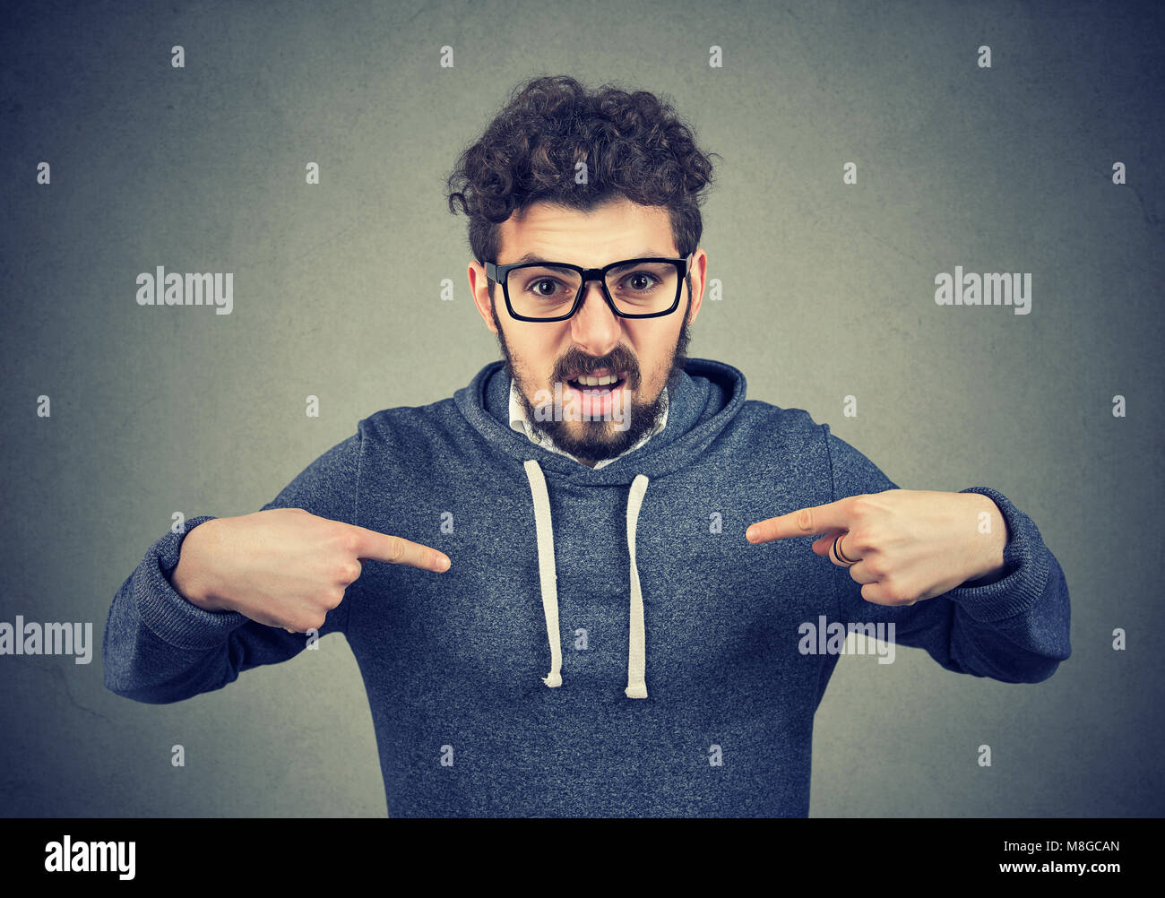 Young angry man in eyeglasses overreacting while pointing at himself looking offended. - Stock Image