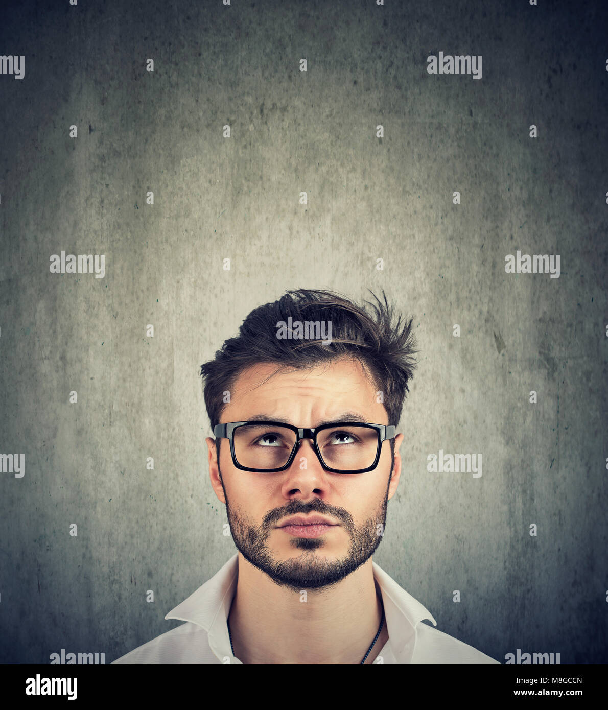 portrait of a young doubtful man with glasses looking up - Stock Image