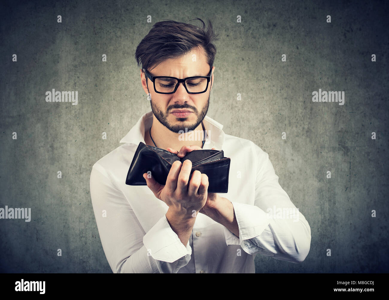 Young handsome man upset with empty wallet having financial difficulties spending all money. - Stock Image