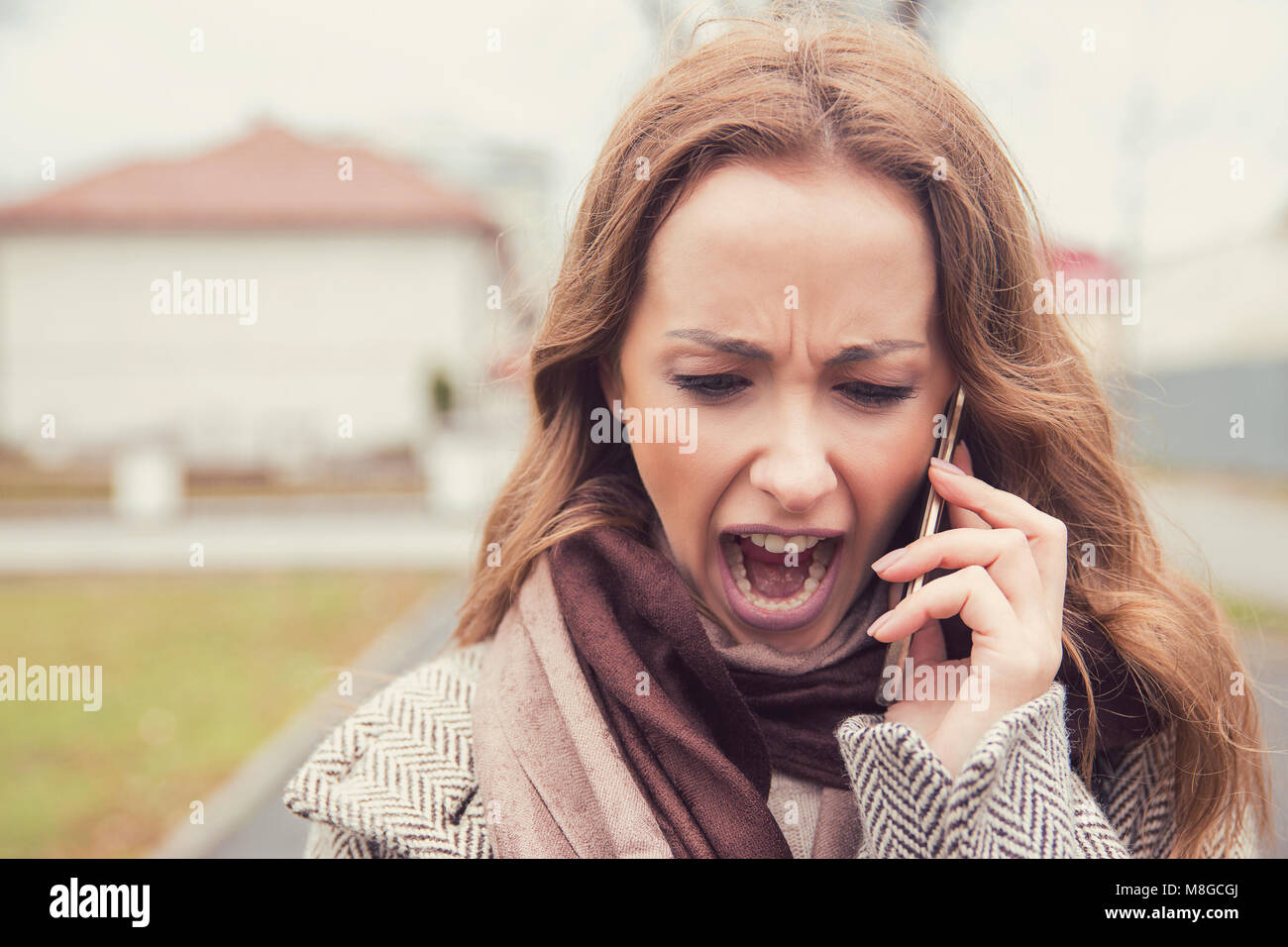 Young brunette in coat talking on a phone outside and screaming in stress having bad breakup. - Stock Image