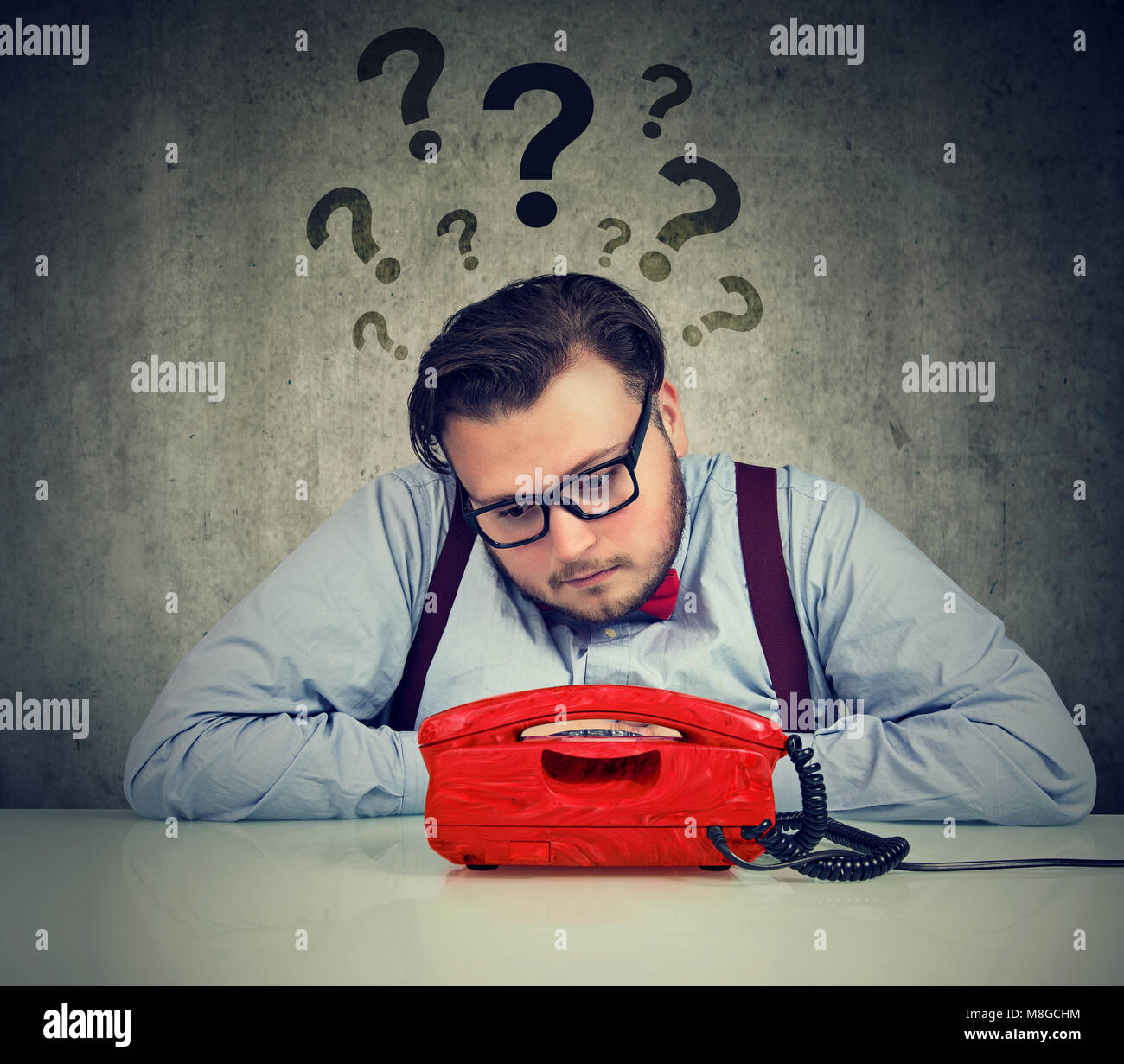 Sad man with too many questions waiting for a call - Stock Image