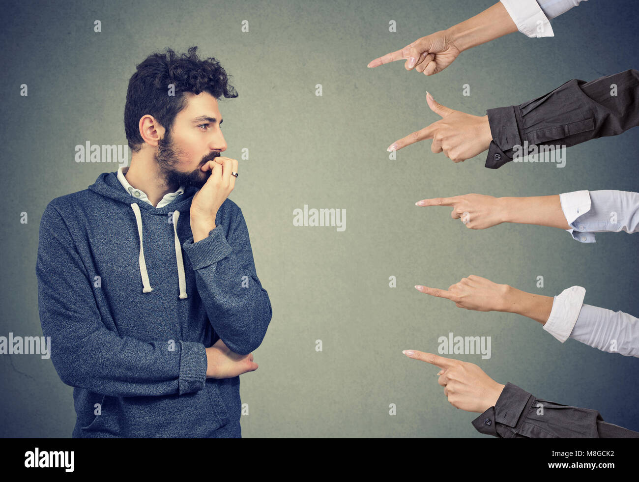 Anxious man judged by different people. Concept of accusation of guilty guy. Negative emotions face expression feeling - Stock Image