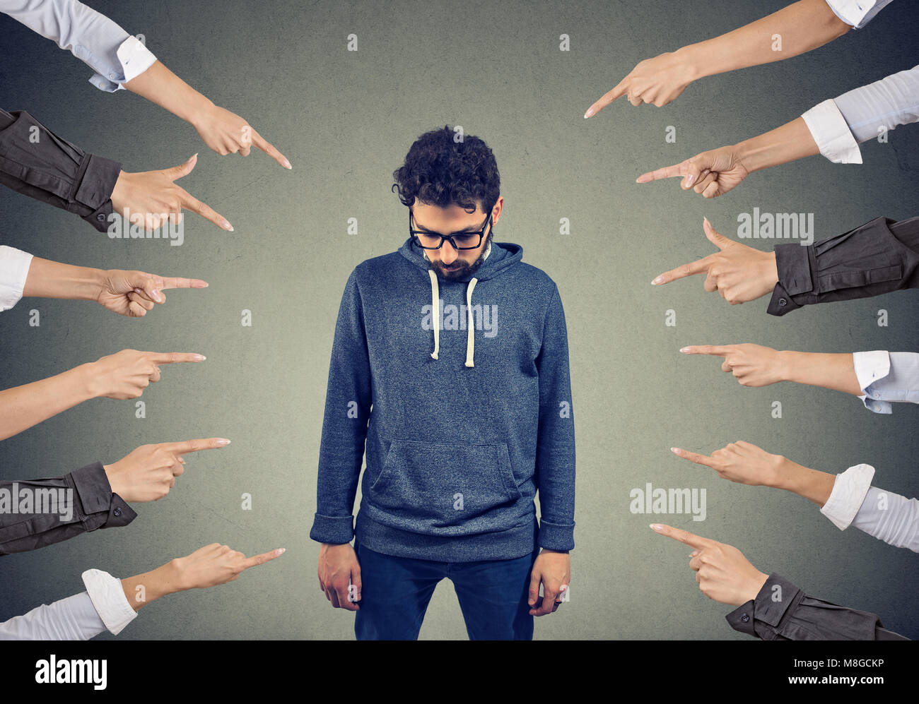 Plenty of crop hands fingers pointing at young man feeling guilty and being introvert. Stock Photo