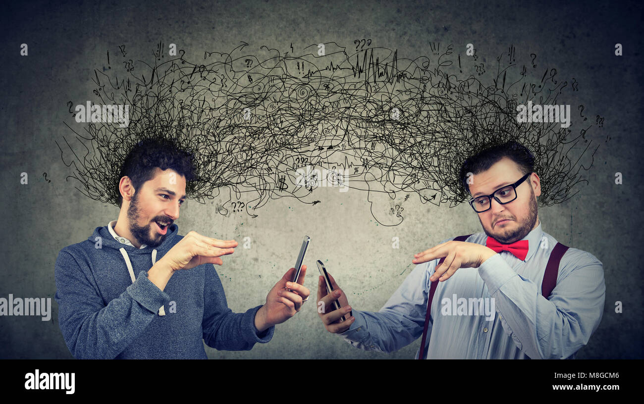 Two men manipulating internet with smarpthones exchanging with multiple ideas and thoughts - Stock Image