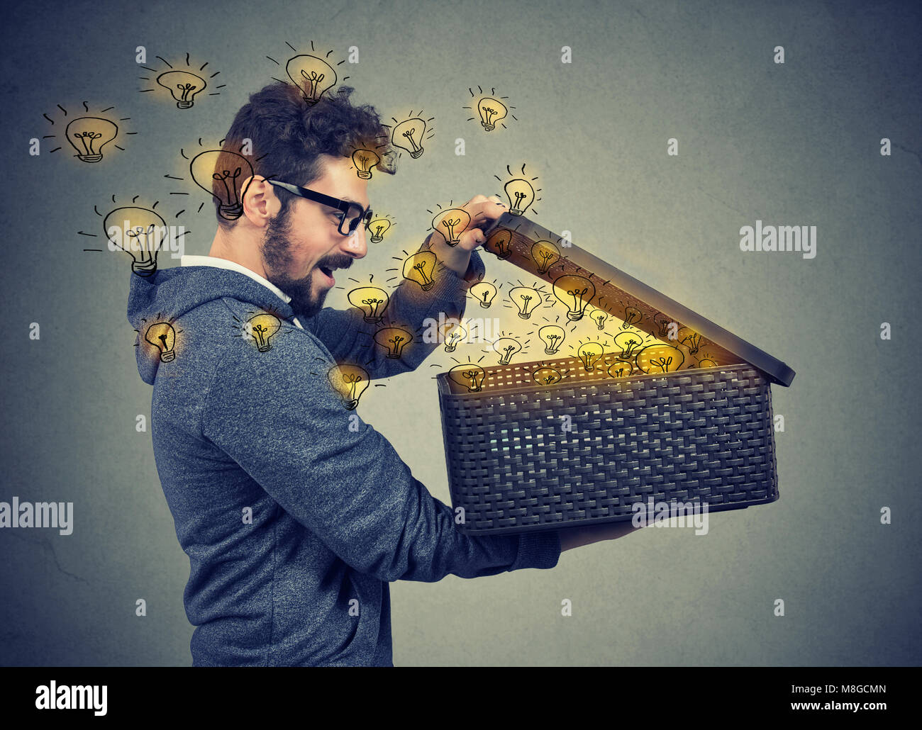 Happy surprised man opening a box with many bright light bulbs flying out - Stock Image
