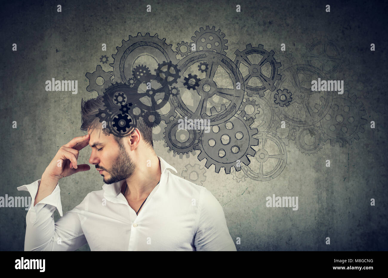 Serious young man thinking very hard solving a problem - Stock Image