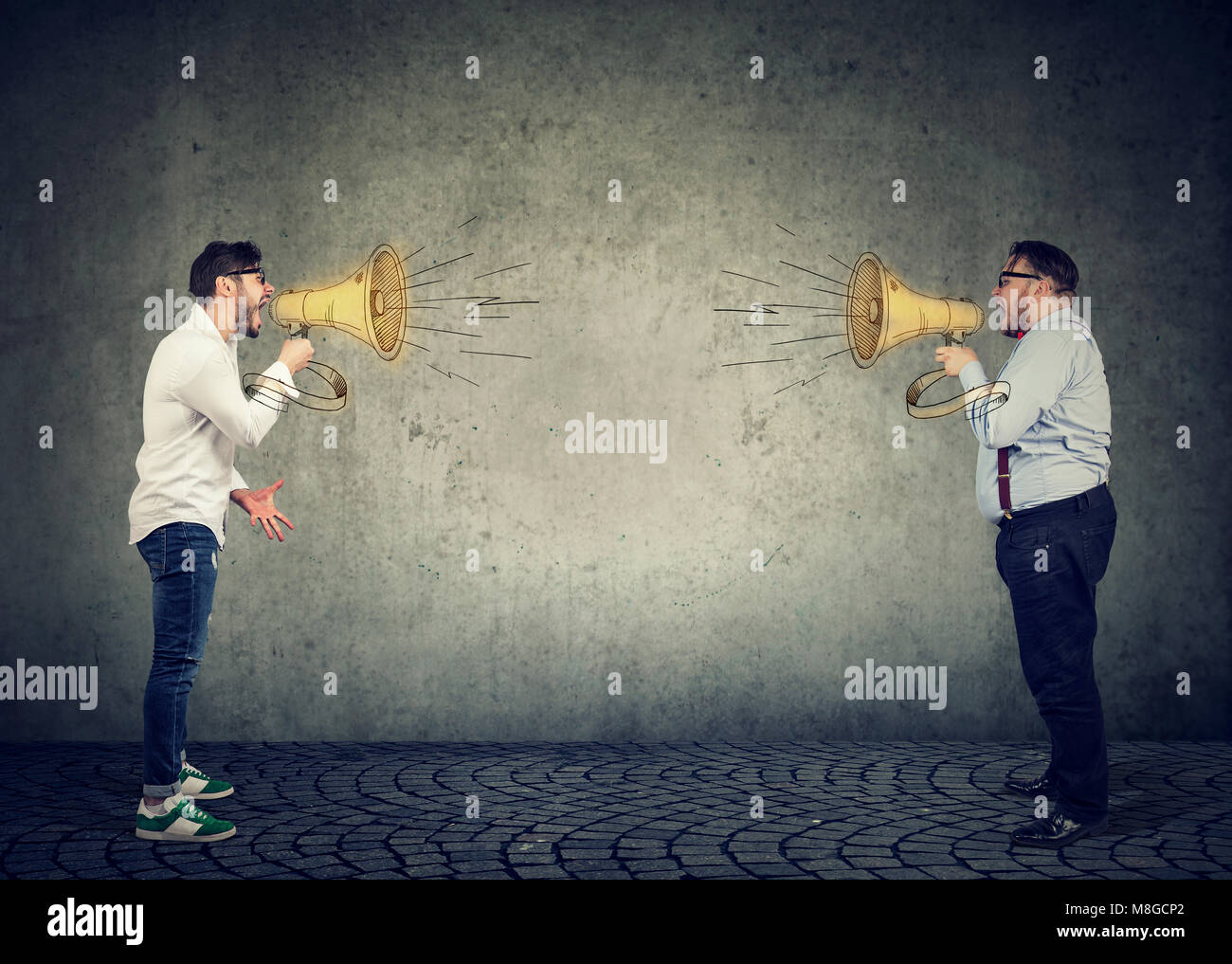 Businessmen screaming into a megaphone at each other having an angry debate - Stock Image