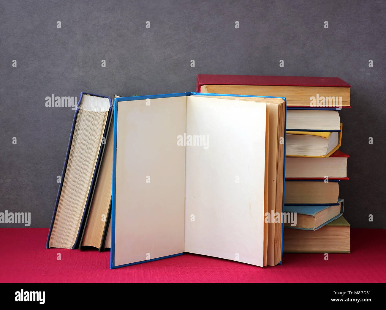 Stack of books in the colored covers on the table with a red tablecloth. Still life with books. - Stock Image
