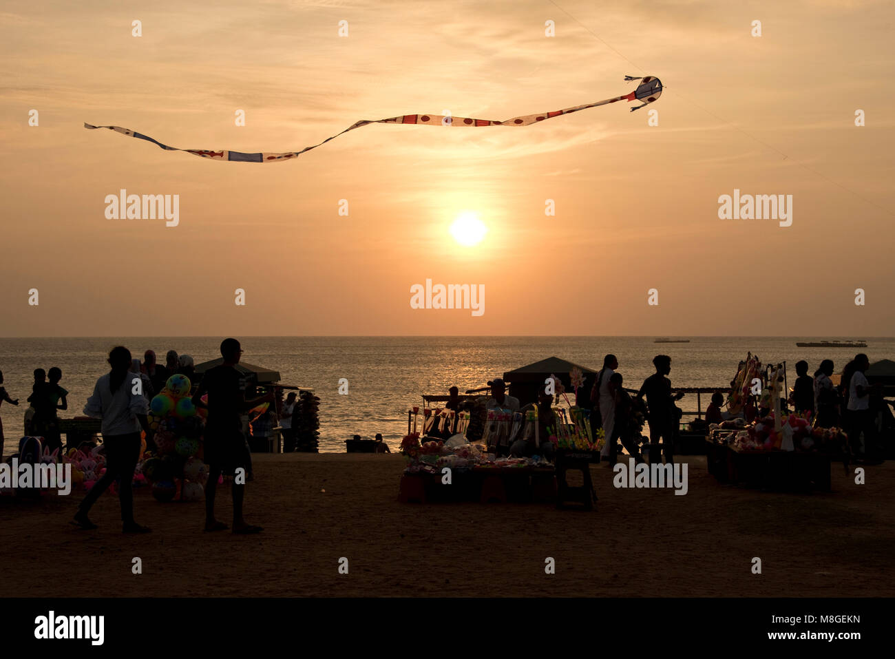 Local people and stall holders with a kite in the air on Galle Face Green at sunset - a popular spot in Colombo to spend time playing by the sea. Stock Photo