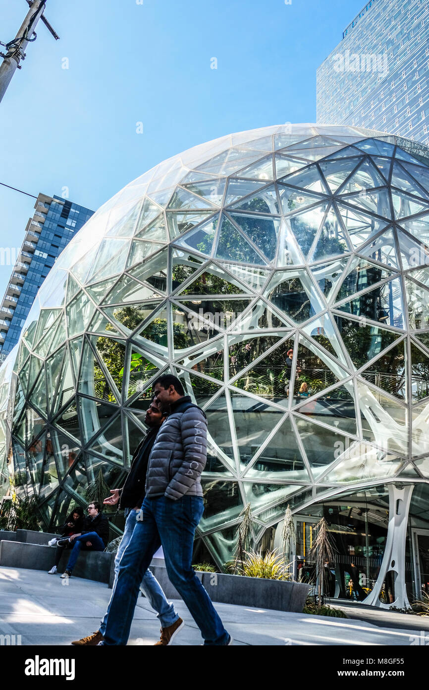 Two foreign workers walk pass the glass dome Spheres at Amazon headquarter in downtown Seattle Stock Photo