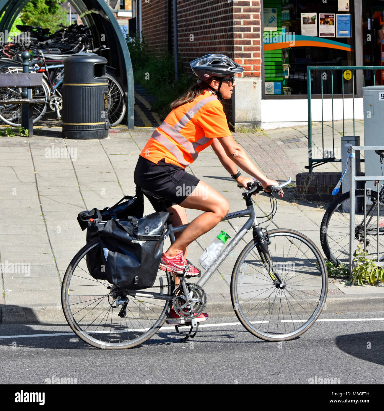 Young woman cycling and exercising by riding a bicycle  wearing bike helmet hard hat & high vis jacket travelling - Stock Image