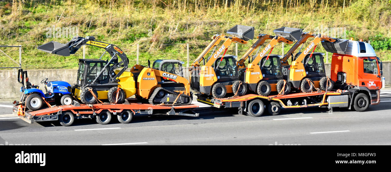 Low loader lorry truck & trailer transport loaded with 6 assorted new Case & New Holland loader equipment - Stock Image