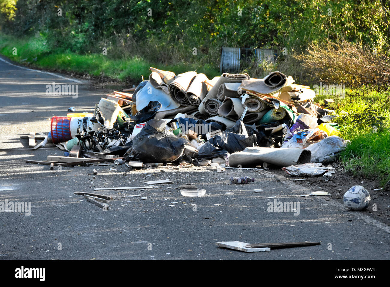 Fly tipping of truck load of assorted waste rubbish garbage dumped on a public highway in a country lane Brentwood - Stock Image