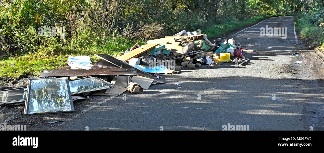 Fly tipping of truck load assorted waste rubbish garbage dumped on public highway in a country lane Navestock Brentwood - Stock Image