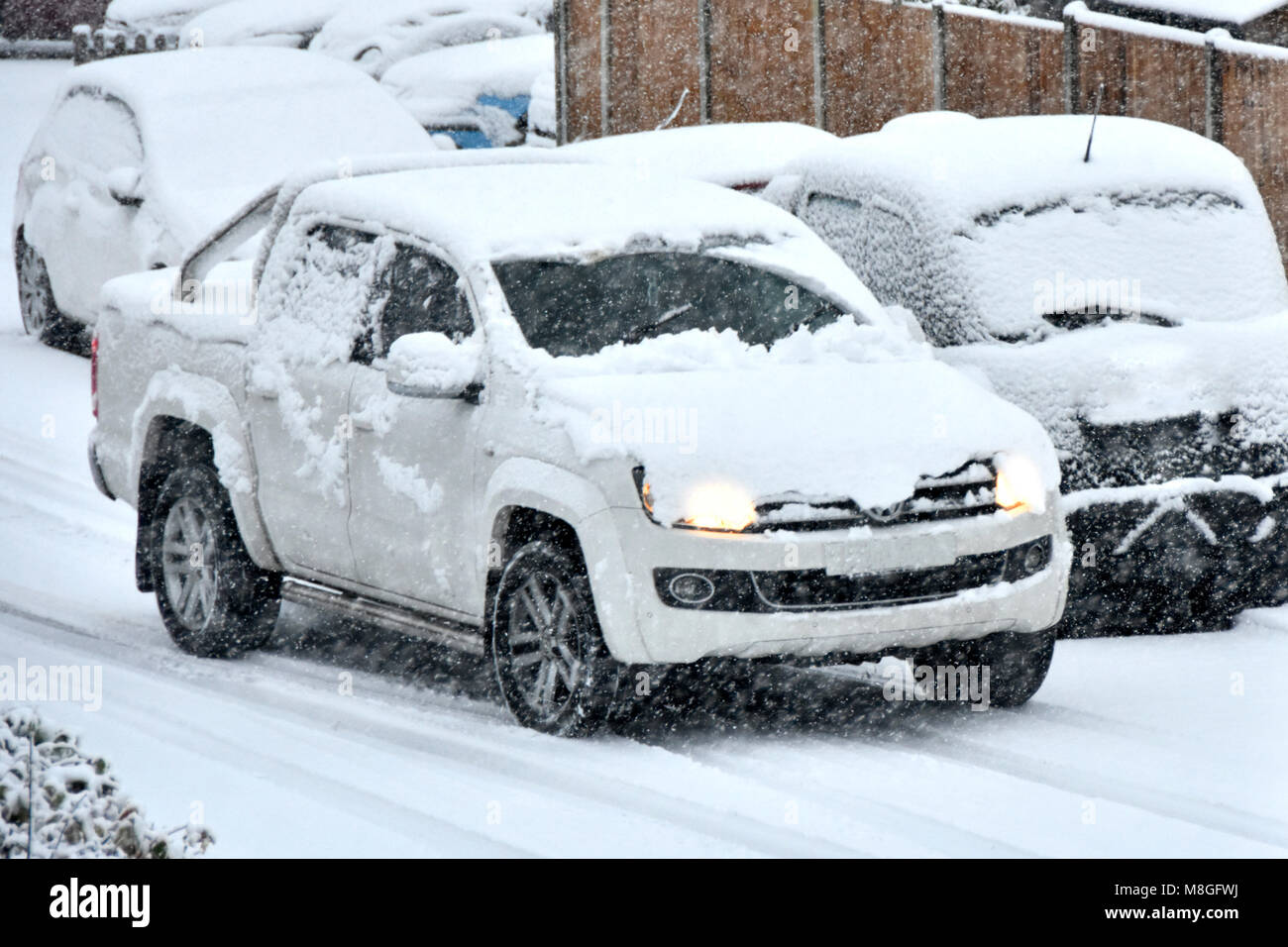 White car covered in snow with headlights on driving past parked vehicles with winter snow falling on snow covered - Stock Image