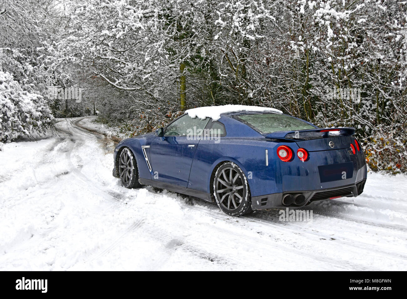 Poor weather for driving Nissan car along snow covered country lane in winter snow scene in snowy rural Brentwood - Stock Image