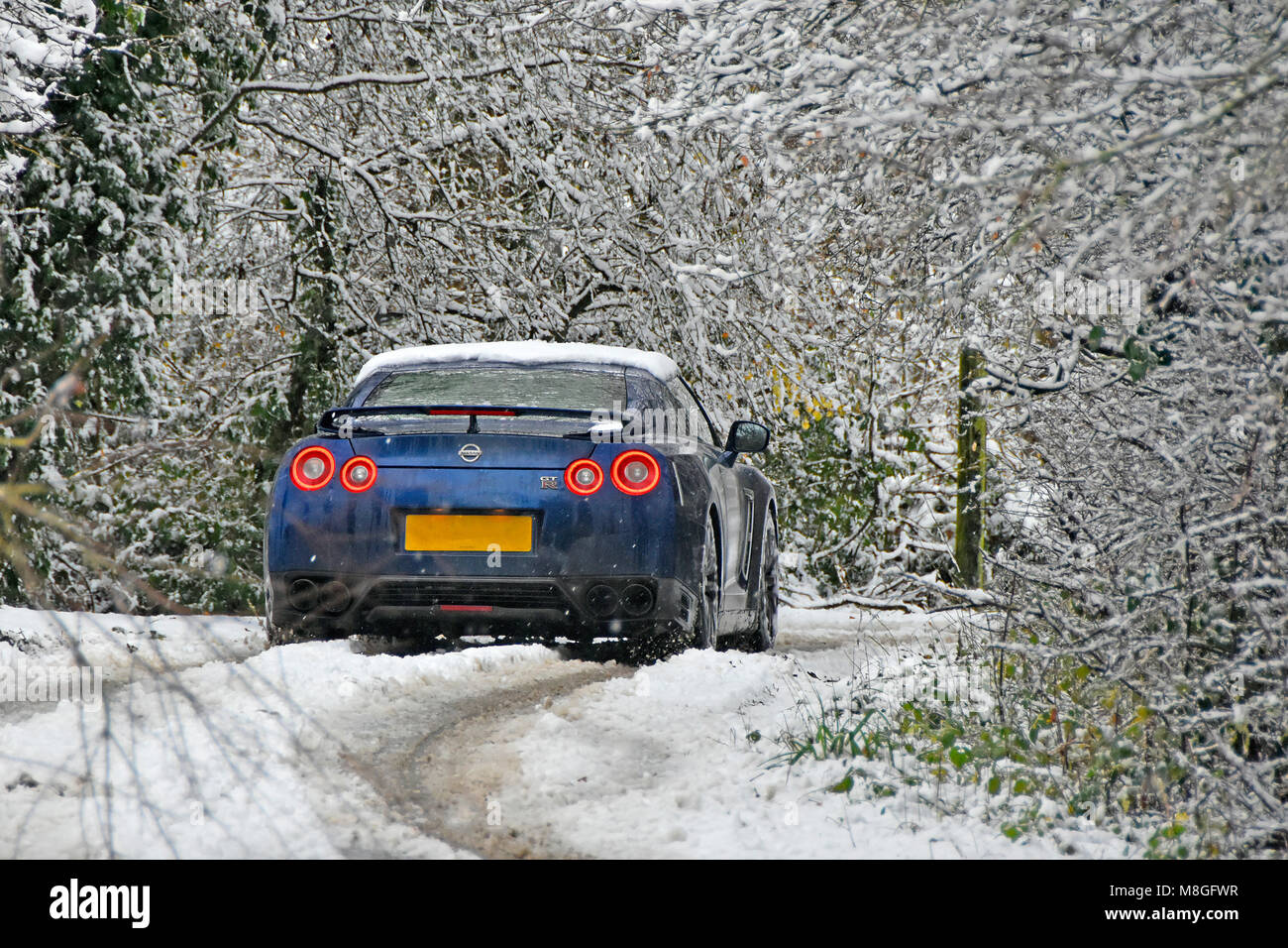 Snowy tree landscape scene driving car in narrow road way down country lane covered in winter snow fall rural home - Stock Image
