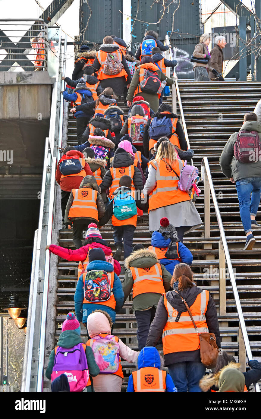 Group of primary school children on school trip in high vis jacket or vest with teacher & assistants climbing - Stock Image