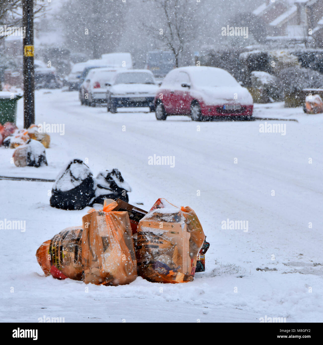 Winter street scene bags of recycle waste & black sack landfill rubbish snow covered on pavement for council - Stock Image