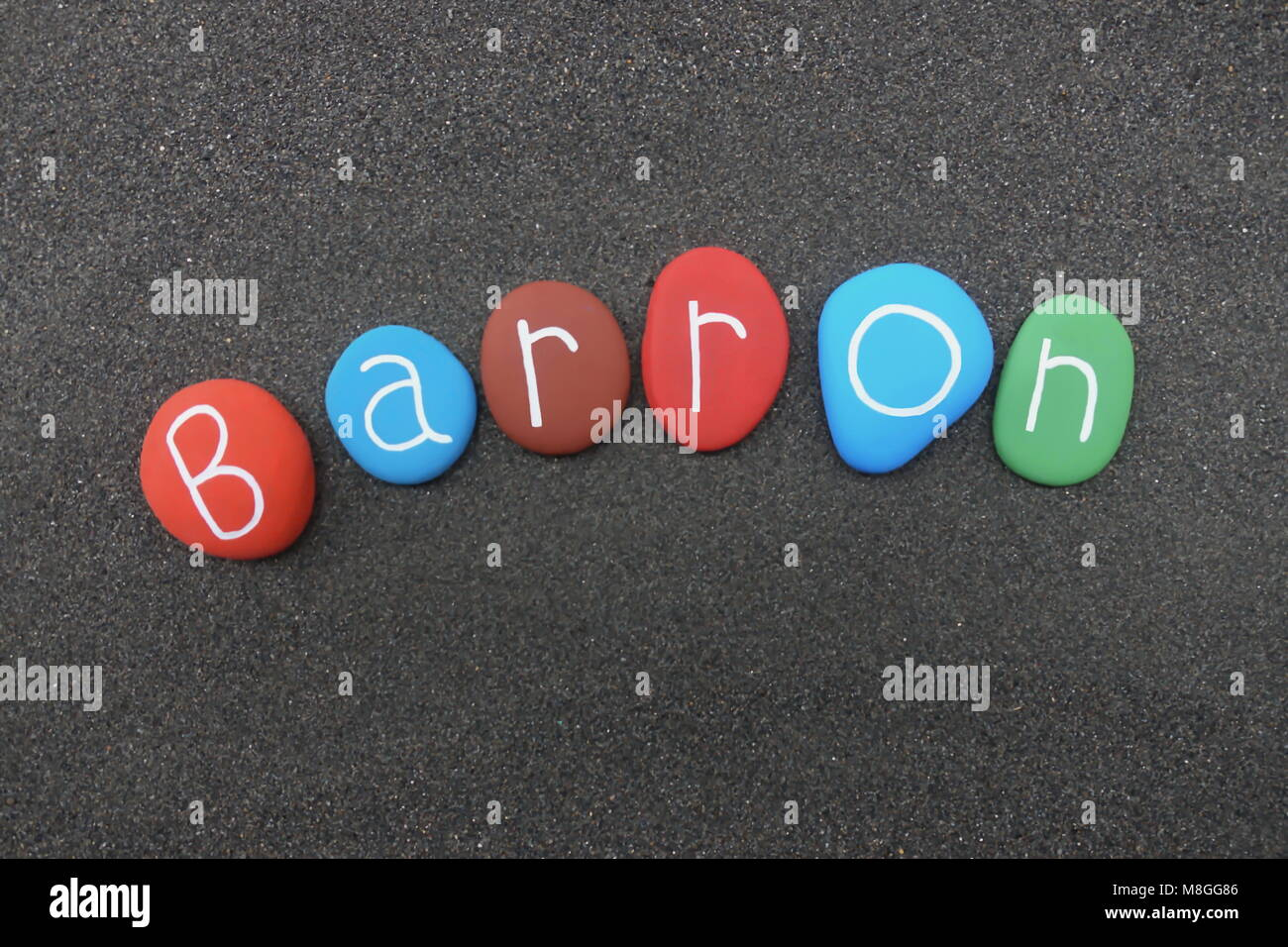 Barron, masculine given name with multicolored stones over black volcanic sand - Stock Image