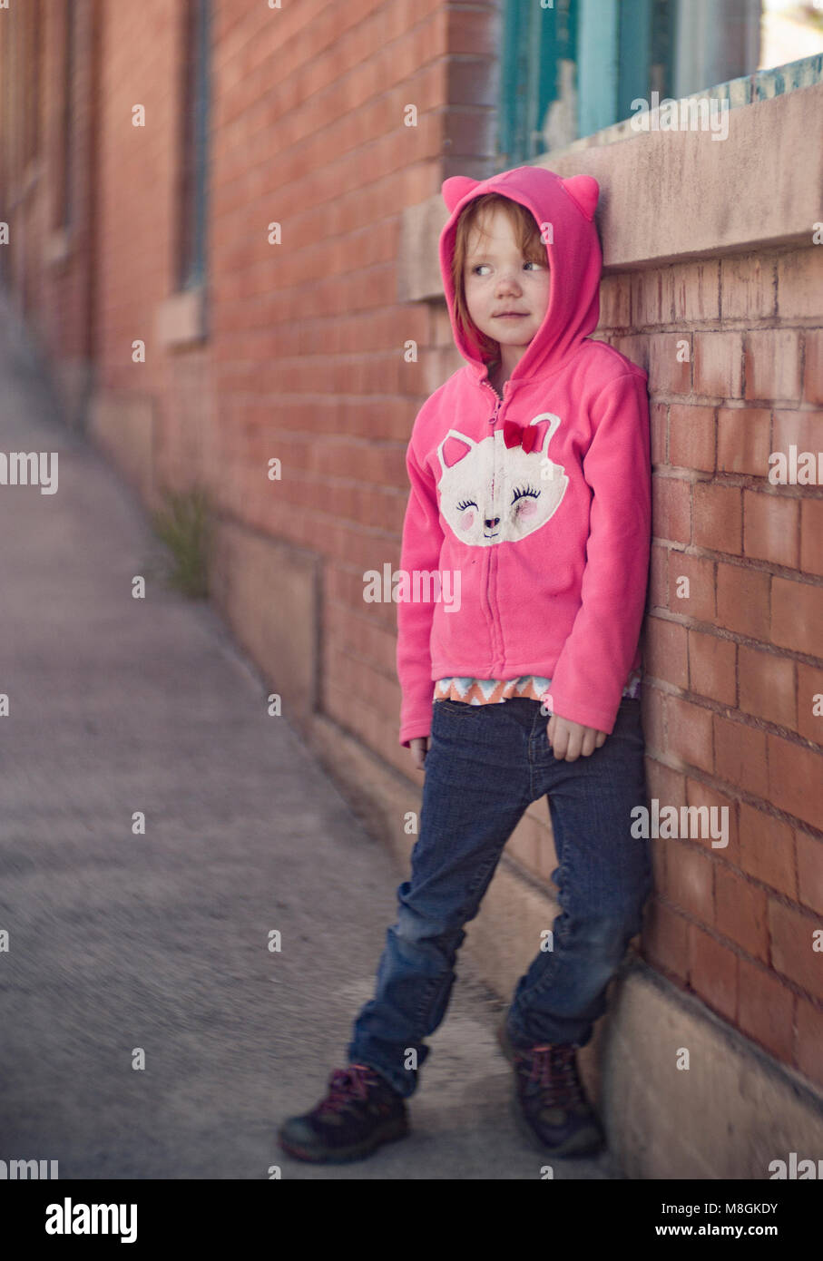 Little red headed girl, leaning against a brick wall, wearing a pink Hello Kitty hoodie.   Canon EOS 6D,  Bausch - Stock Image