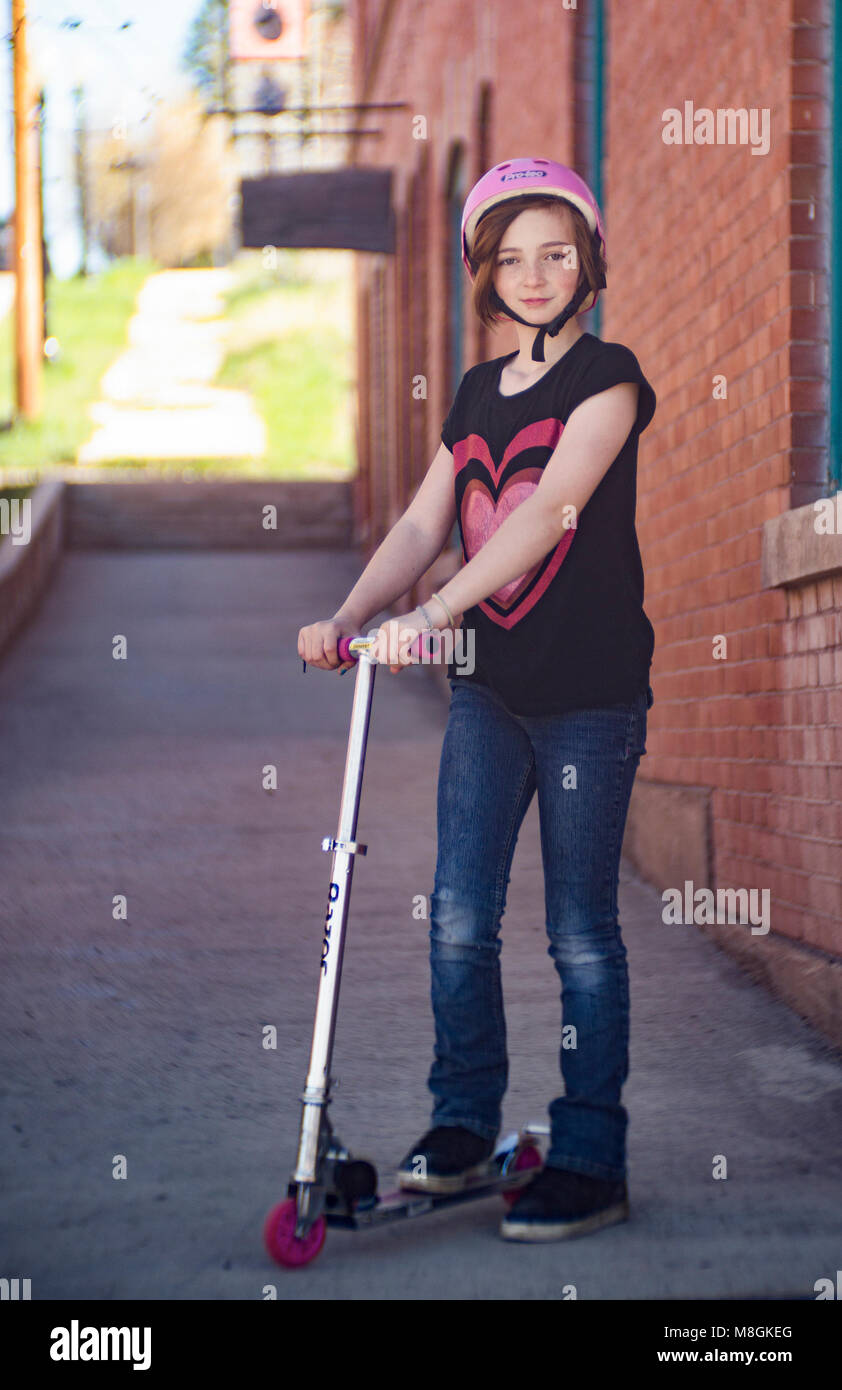 Preteen girl with red hair and freckles, on the sidewalk with her aluminum kick scooter. - Stock Image