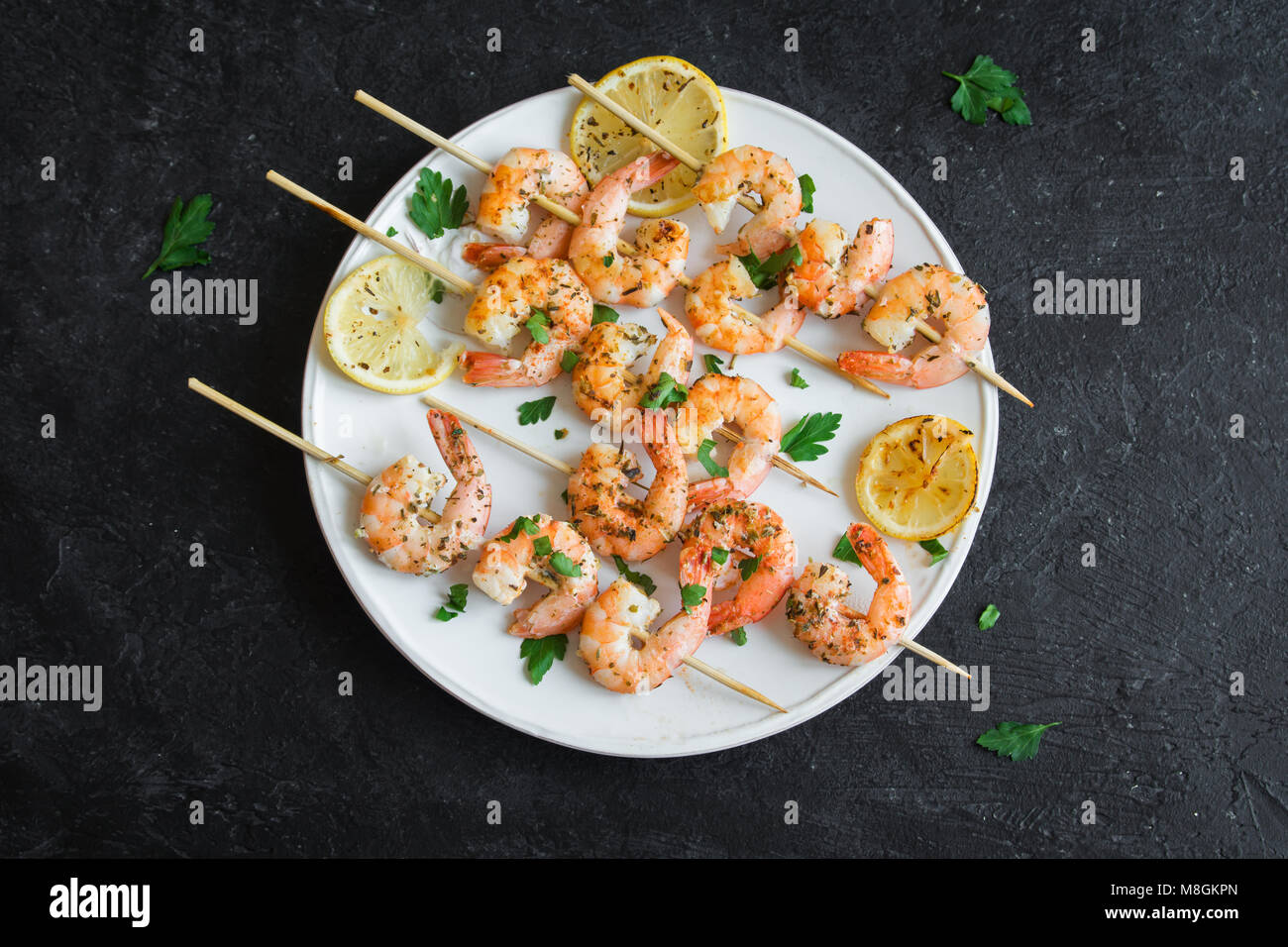 Grilled shrimp skewers. Seafood, shelfish. Shrimps Prawns skewers with spices and fresh herbs on stone black background, - Stock Image