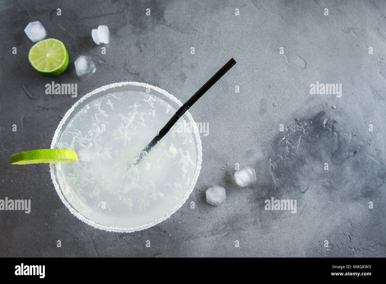 Margarita Сocktail with lime and ice on grey concrete background, copy space. Classic Margarita or Daiquiry Cocktail. - Stock Image