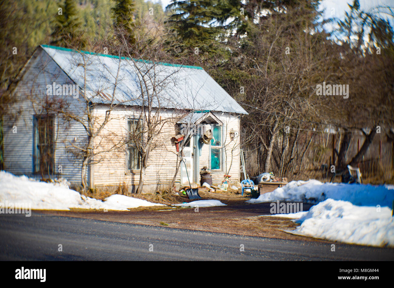 A small white wood frame house, with a messy yard, in the town of Clark Fork, Idaho. - Stock Image
