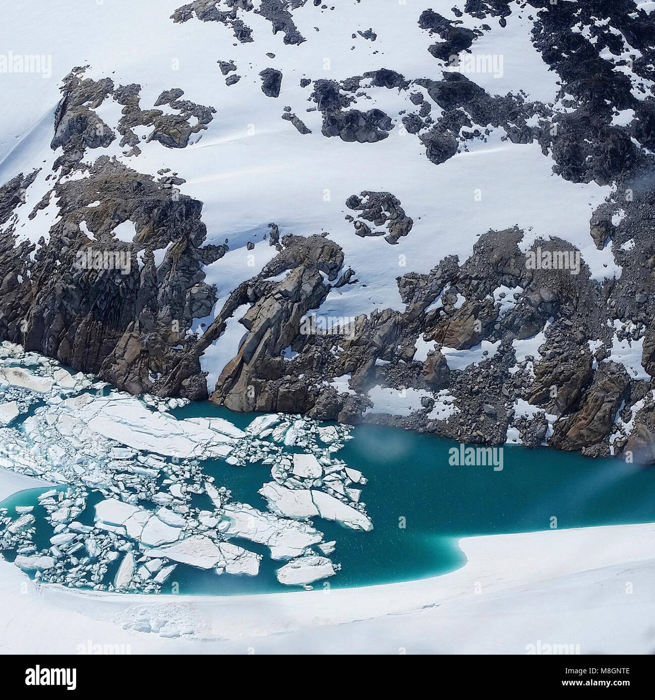 Chigmit Glaciers   .Icebergs float in a small blue lake forming from melting glaciers in the Chigmit Mountains - Stock Image