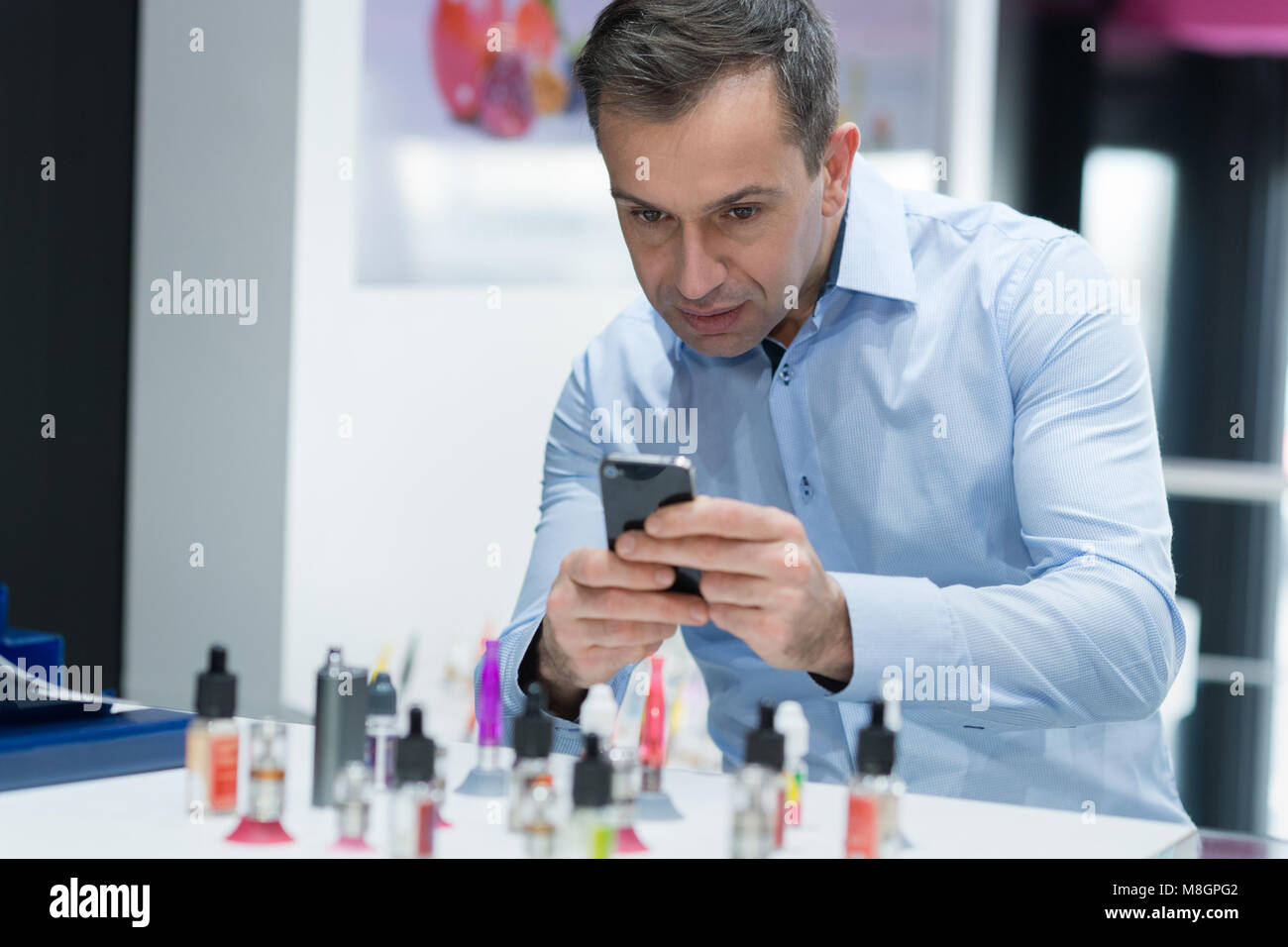 man in vaporizer shop being passed a case - Stock Image