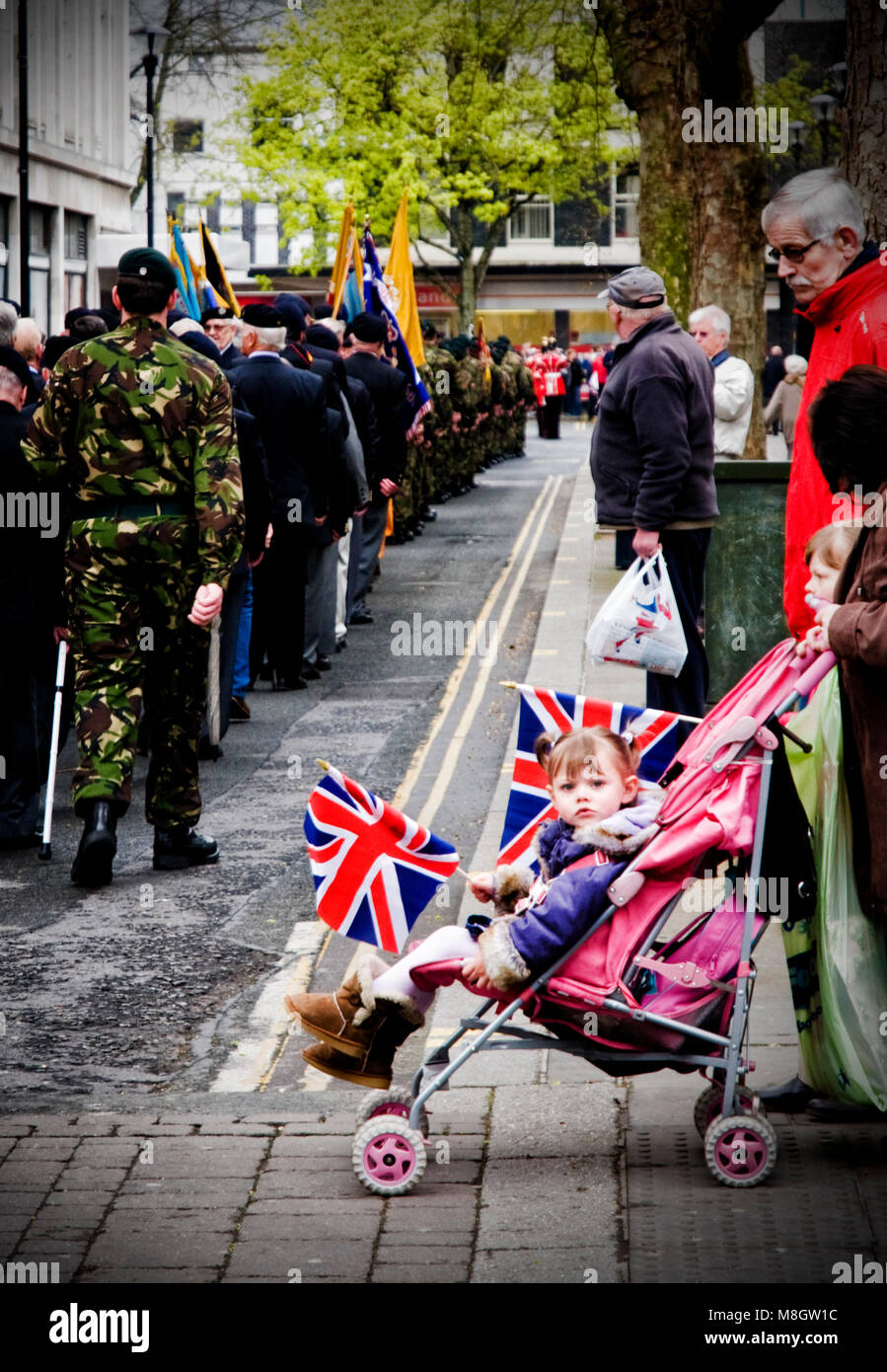 A little girl looks less than impressed at a military parade in Gloucester - Stock Image