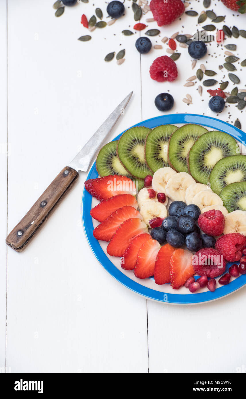 Plate of sliced fruit with seeds on a white wood background Stock Photo
