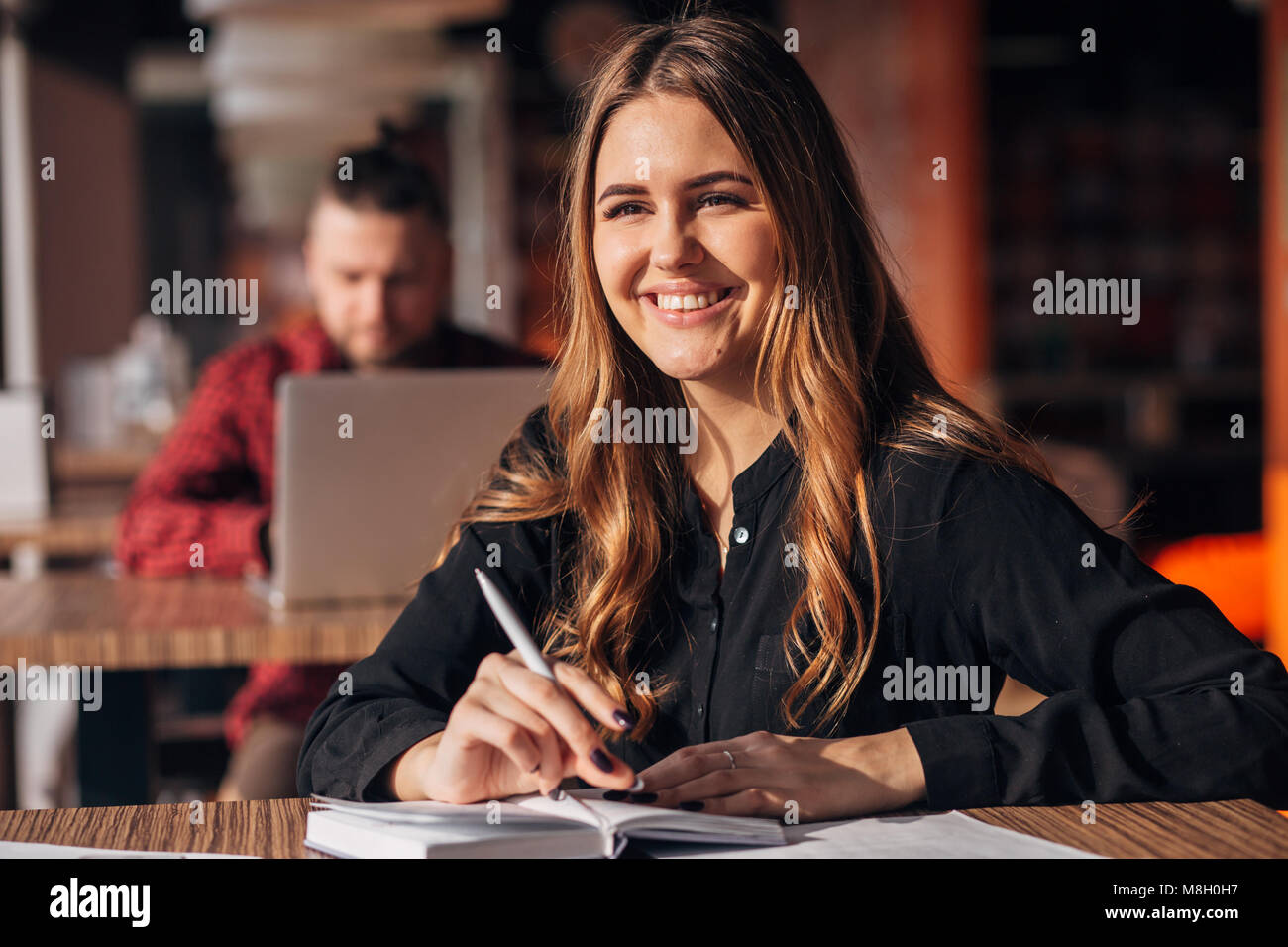 young woman smiling at camera while working remotely in coffee shop. Positive female with notepad - Stock Image