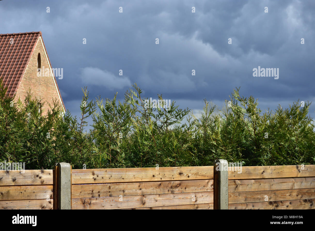Dark rainy clouds, wooden fence, green cypress hedge, wooden fence and brick house - Stock Image