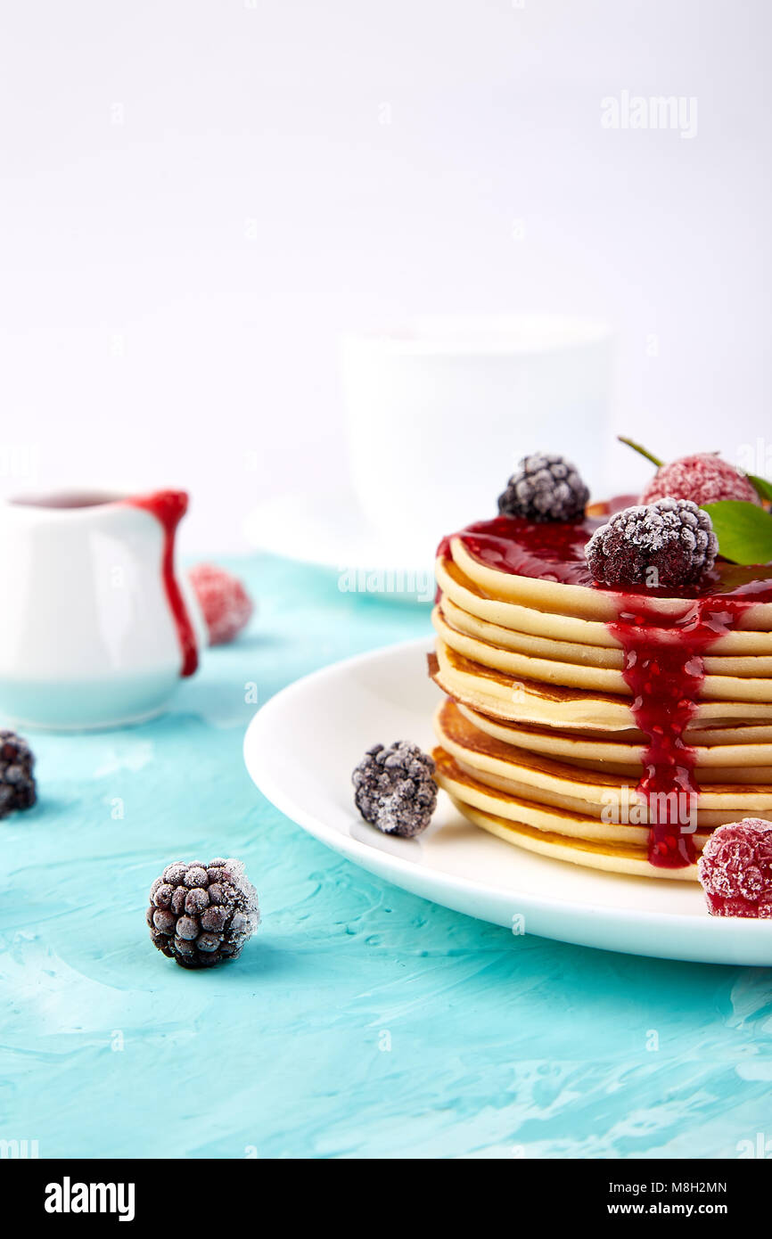 American pancake with jam and frozen raspberry with tea on blue background. - Stock Image