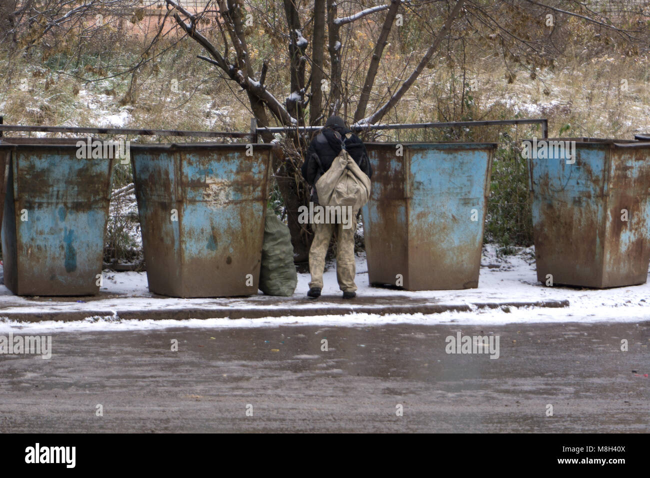 The lame homeless vagrants near the garbage cans looking for empty bottles and leftover food. The problem of homeless - Stock Image
