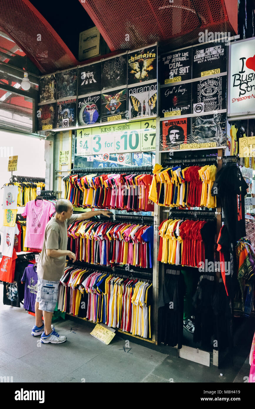Bugis Street, Singapore. A shop keeper or assistant arranges his wall of flashy affordable t-shirts for sale at - Stock Image