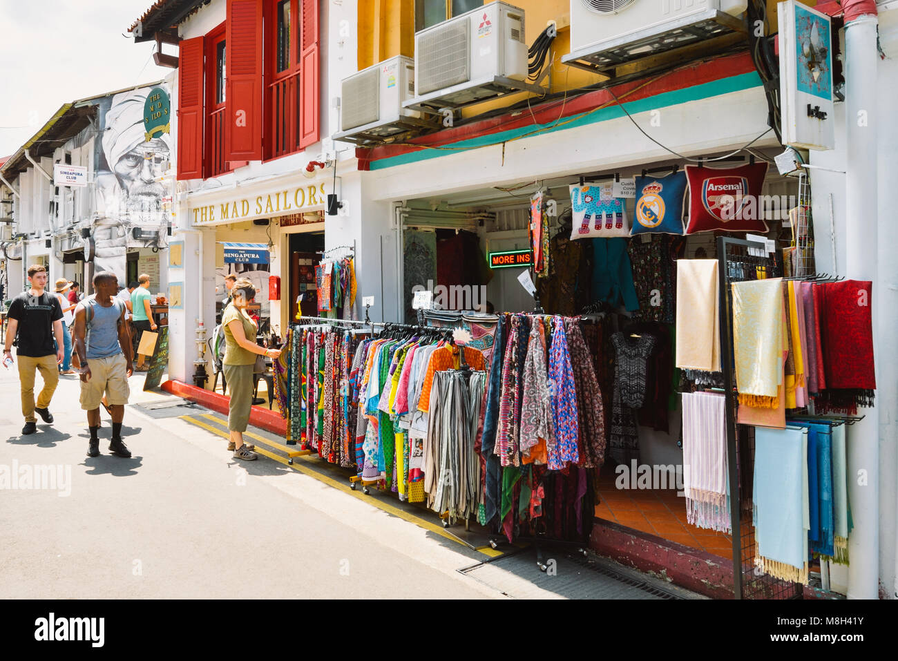 Singapore Haji Lane. Among the pre-war colonial-style shophouses, a tourist browses a rack of colourful arab style - Stock Image